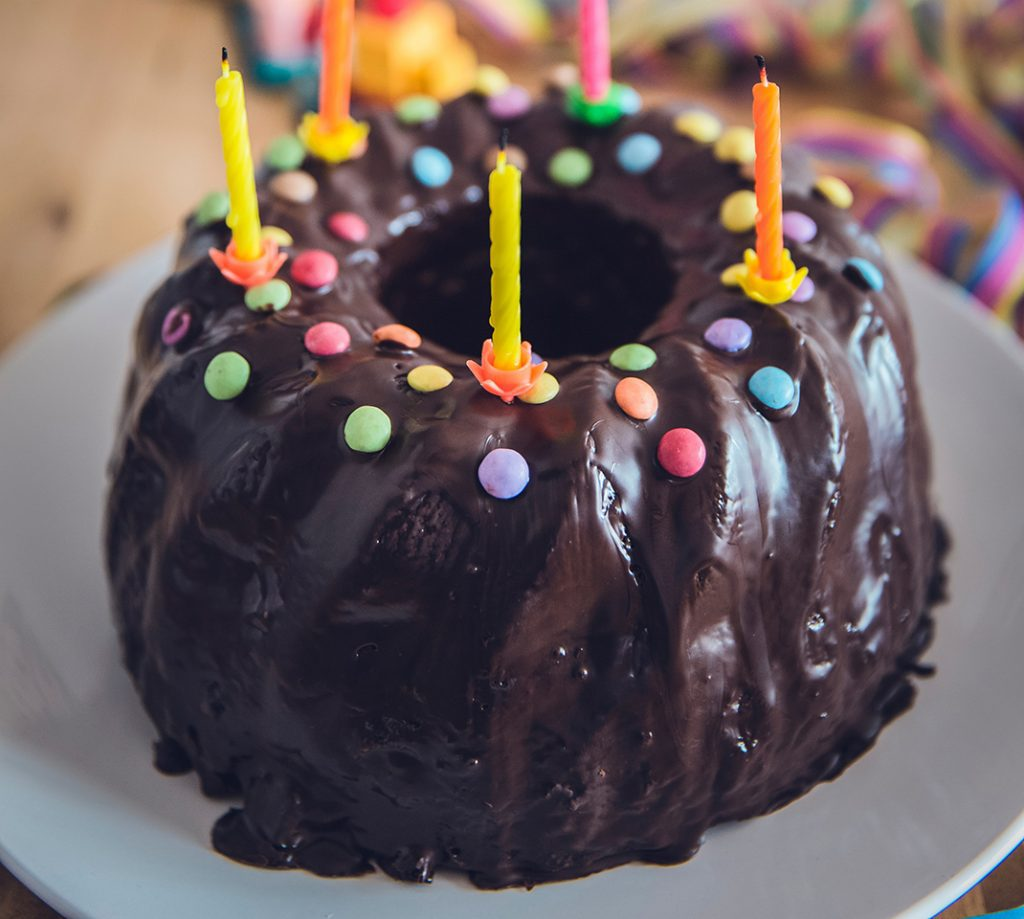 Chocolate bundt cake with 5 candles and sprinkles