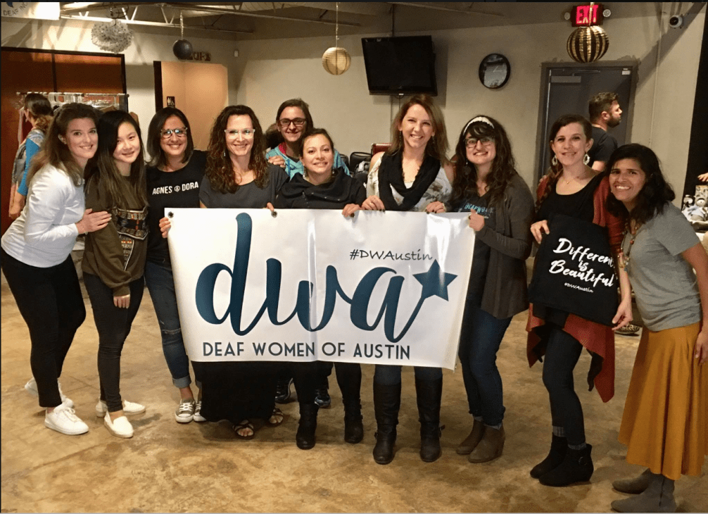 10 members of Deaf Women of Austin, holding up a branded sign and smiling
