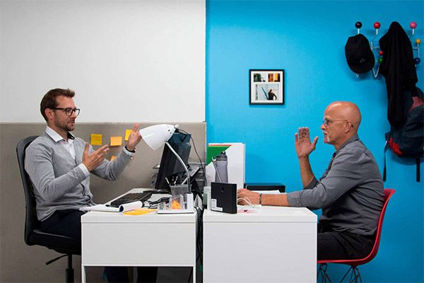 Two men signing to each other through their computers