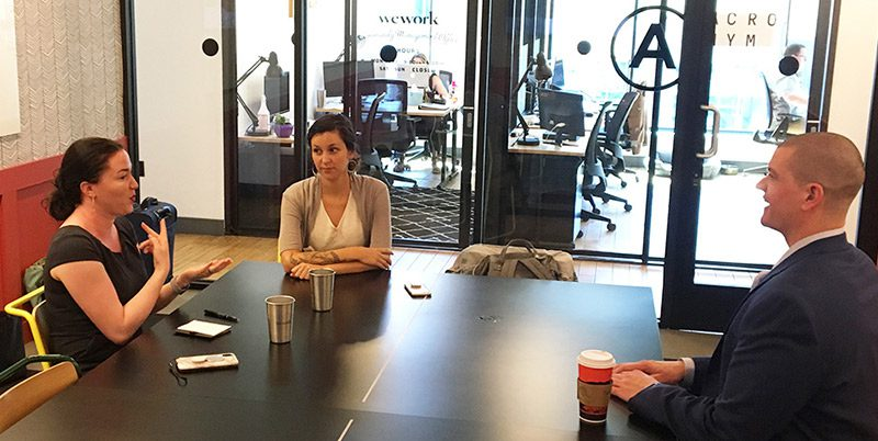 Two women at a conference table with CSD's CEO, Chris Soukup