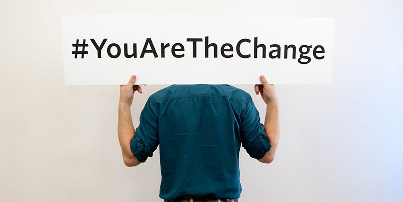 """Person holding a sign over their shoulders that reads """"#You Are The Change"""""""