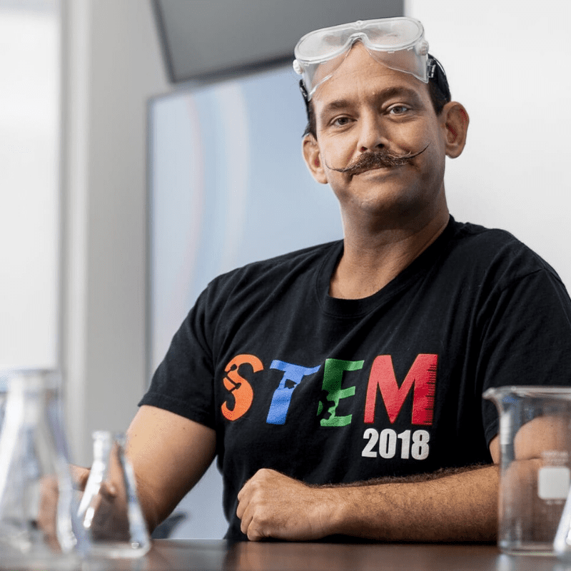Scott Cohen in a STEM tshirt and science goggles