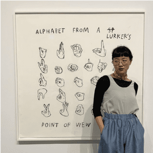 "Woman standing in front of a piece of art called ""Alphabet from a lurker's point of view"""