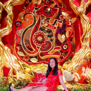 Woman sitting down in front of an elaborate red and gold piece of artt