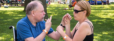 Photograph of a man and woman communicating use pro-tactile sign language