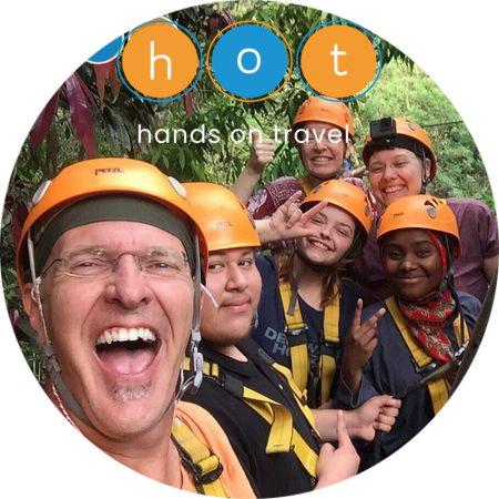 Photo of a group on a zipline platform with the Hands on Travel logo