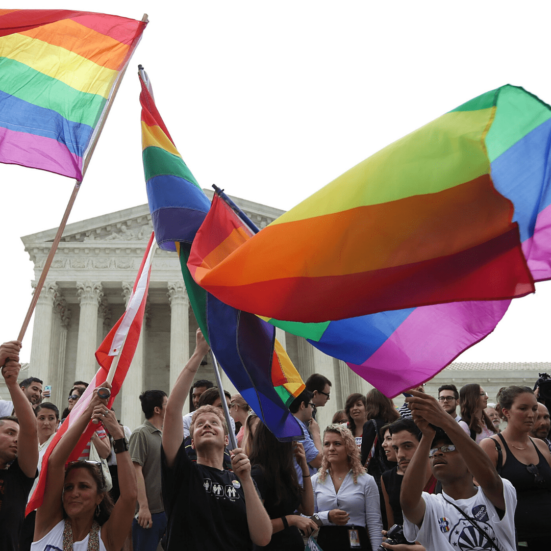 Group of people waving the LGBTQ+ flag in front of the Lincoln Memorial