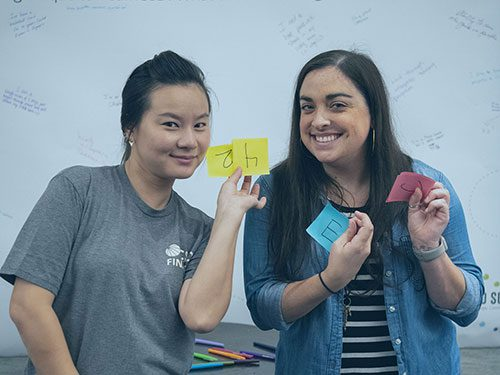 Two women standing in front of a white board, smiling and holding up two post-it notes each
