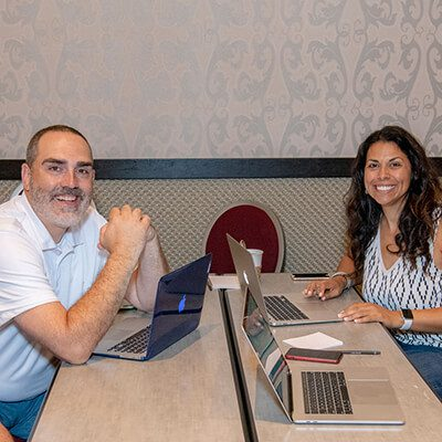 A man and a woman sitting at a desk with lap tops smiling into the camera