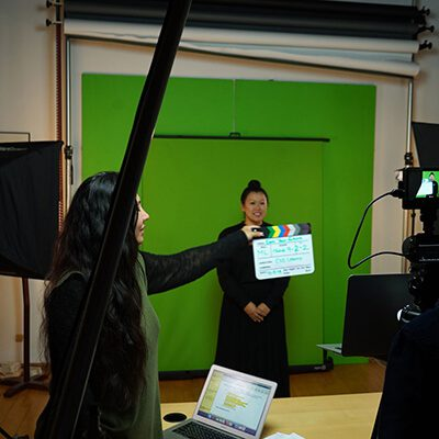A woman standing in front of a green screen, with another woman holding a cut board in front of a camera