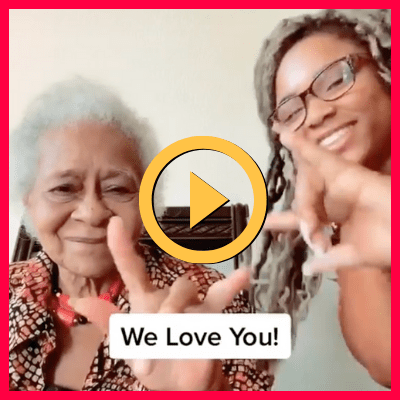 """Two Black women signing """"I love you"""" into a camera"""